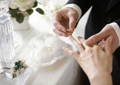 Stock Photo of Groom putting a ring on bride's finger