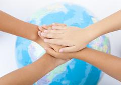 Overlapping hands and a globe Stock Photos