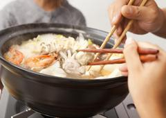 Parents and children eating Japanese nabe - stock photo