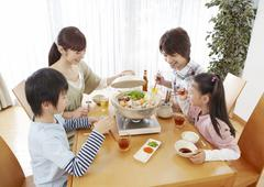 Parents and kids sitting around Japanese hot pot - stock photo