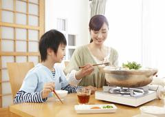 Mother and son sitting around Japanese hot pot - stock photo