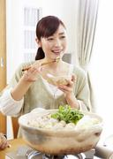 Young woman eating Japanese hot pot - stock photo