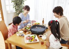 Parents and kids eating Japanese barbeque Stock Photos