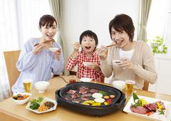 Parents and kids eating Japanese barbeque - stock photo