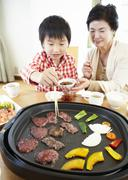 Grandmother and grandson eating Japanese barbeque - stock photo
