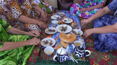 Traditional Central Asian meal, ladies eating lunch, table, colorful dresses Stock Footage