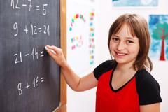 school girl writing solution on chalkboard - stock photo