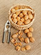 Walnut in basket and nut cracker Stock Photos
