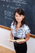Stock Photo of proud math teacher with book