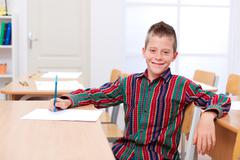 confident boy sitting alone in classroom - stock photo