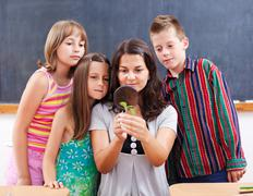 teacher and students look at plant - stock photo