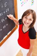 Schoolgirl looking up in front of chalkboard Stock Photos