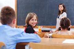 Cheerful schoolgirl in class room Stock Photos