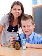 wise boy with microscope and teacher - stock photo