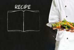 chef with recipe book on chalk blackboard menu background - stock photo