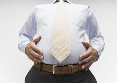 Businessman touching his belly Stock Photos