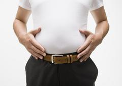 Man touching his belly - stock photo