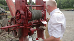 Man paints colliery hoist with red lead or red oxide Stock Footage