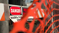 Danger sign behind orange barrier fencing - stock footage
