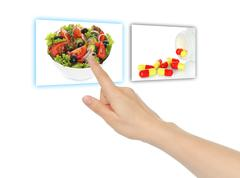 Hand pushing virtual salad instead of pills . Stock Photos