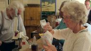 Stock Video Footage of woman puts salt and vinegar onto chips at edwardian fish and chip shop