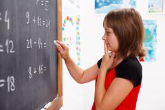 girl standing in front of chalkboard and thinking - stock photo