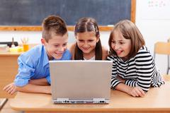 Stock Photo of happy kids looking at laptop