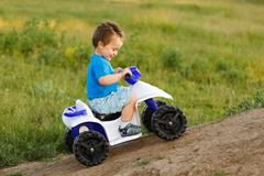 Little boy driving off road toy quad Stock Photos