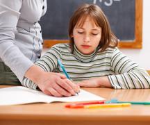 teacher showing writing to schoolgirl - stock photo