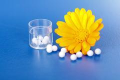 calendula officinalis and homeopathic pills - stock photo
