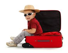 confident little boy wearing straw hat, sitting in suitcase - stock photo