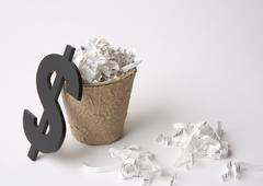 Shredder dust in a trash can and dollar sign Stock Photos