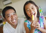 Stock Photo of Father and daughter eating ice pop