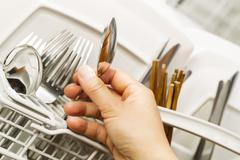 checking for cleanliness of silverware from dishwasher - stock photo