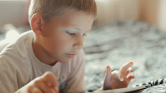 Little boy playing on the tablet computer games Stock Footage