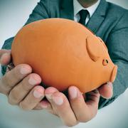Man in suit with a piggy bank Stock Photos