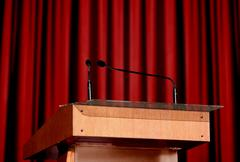 microphone and podium with red curtains - stock photo