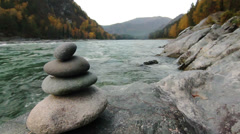 Pyramid of stones on the bank of a mountain river in Altay Stock Footage