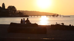 Friends watching sunset at the beach Stock Footage