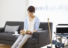 Senior woman reading a book on a sofa and a wheelchair - stock photo