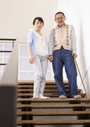 Senior couple going down stairs - stock photo
