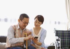 Senior couple using a smartphone on a sofa - stock photo