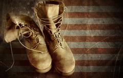 us army boots on the old paper flag background - stock photo