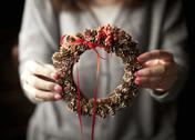 Stock Photo of Woman holding a pinecone wreath