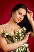 Stock Photo of portrait of a sexy young woman in  corset  against red  background