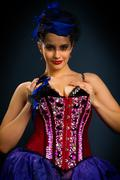 Girl in a red corset on a dark background Stock Photos