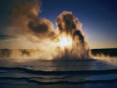 usa, wy, yellowstone np, geyser erupting at sunset - stock photo