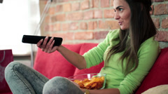 Young woman eating chips and watching tv on sofa HD - stock footage