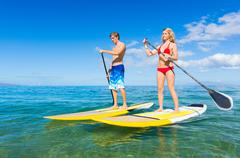 Stock Photo of couple stand up paddle surfing in hawaii