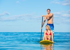 couple stand up paddle surfing in hawaii - stock photo
